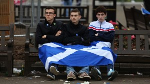 Revelers wrapped in a St Andrew's or Saltire flag, the national flag of Scotland, sit on a bench following Scottish independence referendum result night celebrations in George Square in Glasgow, U.K., on Friday, Sept. 19, 2014. Scotland voted to remain in the U.K. after an independence referendum that put the future of the 307-year-old union on a knife edge and risked years of political and financial turmoil. Photographer: Chris Ratcliffe/Bloomberg via Getty Images