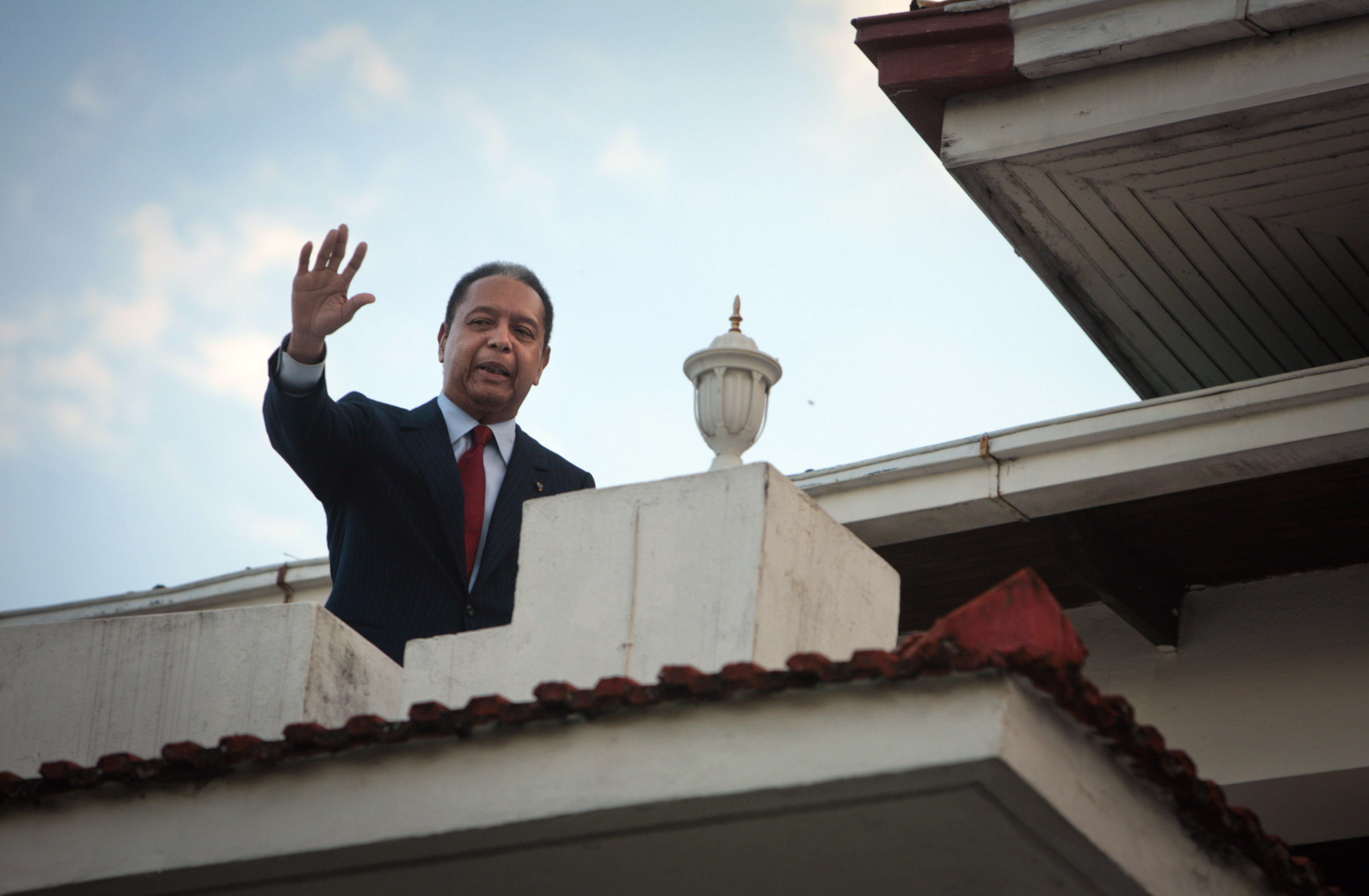 "PORT-AU-PRINCE, HAITI - JANUARY 21:  Former leader of Haiti Jean-Claude ""Baby Doc"" Duvalier waves from a balcony following a press conference at his house in Petionville January 21, 2010 in Port-au-Prince, Haiti. Duvalier returned from exile earlier this week and was questioned by authorities before being released. His critics accuse him of stealing from the treasury during his rule and for crimes against humanity.  (Photo by Lee Celano/Getty Images)"