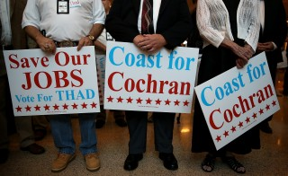 Voters in Gulfport, Mississippi, hold signs for republican Sen. Thad Cochran. Photo by Justin Sullivan/Getty Images