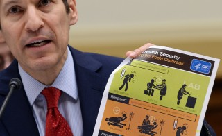 "US Centers for Disease Control and Prevention, CDC, Director Tom Frieden shows an awareness poster as he testifies before Africa, Global Health, Global Human Rights and International Organizations Subcommittee hearing on ""Combating the Ebola Threat"" at the Rayburn House Office Building in Washington, DC, on Aug. 7, 2014. Photo by Jewel Samad/AFP/Getty Images"