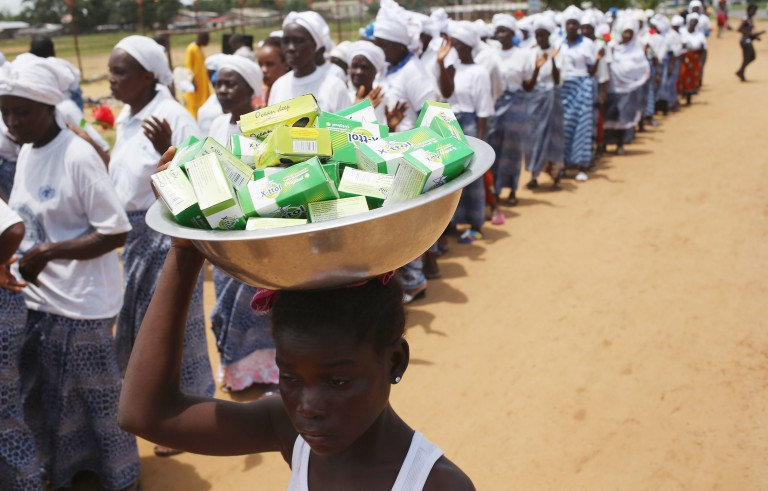 A girl sells soap as women pray for an end to the Ebola epidemic in Monrovia, Liberia on Aug. 14, 2014. Photo by John Moore/Getty Images