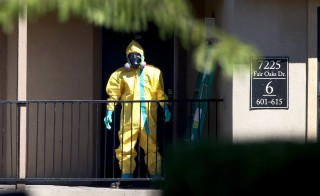 A hazmat team member arrives to clean a unit at the Ivy Apartments, where the confirmed Ebola virus patient was staying, on October 3, 2014 in Dallas, Texas. Public health experts are saying the government has constitutional authority to conduct screenings and quarantines for Ebola. Photo by Joe Raedle/Getty Images