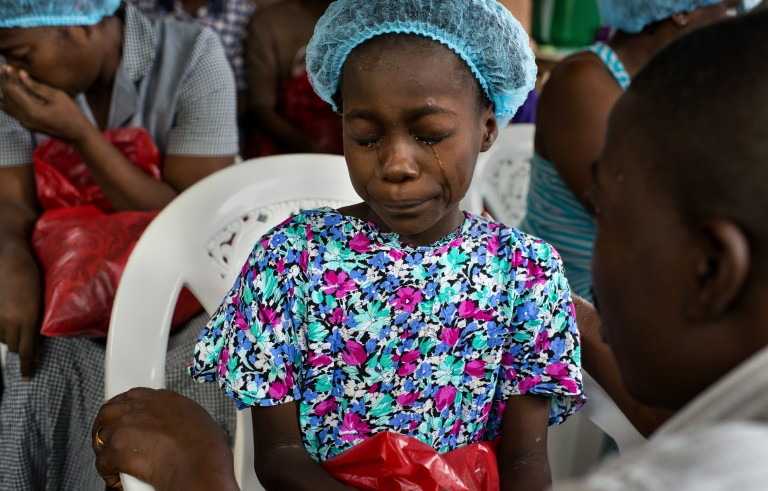 Dr. Jerry Brown tries to comfort Esther Tokpah, 11, before she was released from care on Sept. 24 in Monrovia, Liberia. She lost both parents to Ebola. Photo by Michel du Cille/The Washington Post via Getty Images