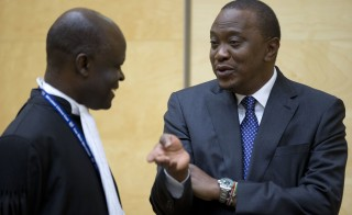 Kenya's President Uhuru Kenyatta, right, talks to a member of his defense team as he appears before the International Criminal Court in The Hague, The Netherlands, on Oct. 8. He is charged with crimes against humanity for allegedly instigating violence after Kenya's 2007 disputed presidential elections. Photo by Peter Dejong/AFP/Getty Images
