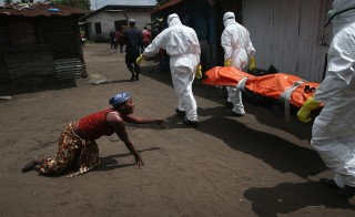 A woman grieves as the body of her sister is carried away by an Ebola burial team to be cremated on Oct. 10 in Monrovia, Liberia. The burial of loved ones is important in Liberian culture, making the removal of infected bodies for cremation all the more traumatic for surviving family members. Photo by John Moore/Getty Images