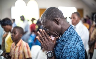 A man prays for those who died of Ebola at St. Joseph Parish Catholic Church in Monrovia, Liberia on Oct. 12. Photo by Mohammed Elshamy/Anadolu Agency/Getty Images