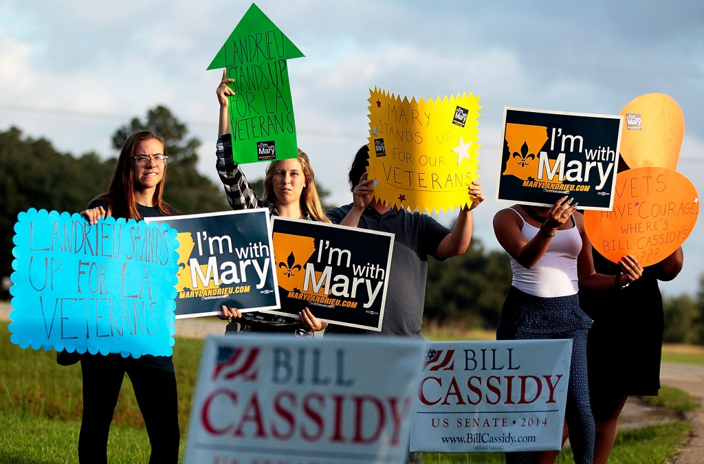 Caption:COVINGTON, LA - OCTOBER 13: Supports of U.S. Senator Mary Landrieu (D-LA) holds up signs for their candidate as U.S. Sen candidate and U.S. Rep. Bill Cassidy (R-LA) (L) and U.S. Senator John McCain (R-AZ) (2nd L) arrive for a Veterans rally at the American Legion Post on October 13, 2014 in Covington, Louisiana. Cassidy is running against incumbent U.S. Sen. Mary Landrieu (D-LA). Photo by Sean Gardner/Getty Images