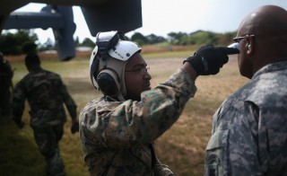 A U.S. Marine checks the temperature of Maj. Gen. Darryl Williams, commander of U.S. Army Africa, before boarding an MV-22 Osprey tiltrotor aircraft on October 15, 2014 in Tubmanburg, Liberia. The general visited the site of the first of 17 Ebola treatment centers being constructed by Liberian forces under American supervision as part of Operation United Assistance to combat the Ebola epidemic. (Photo by John Moore/Getty Images)
