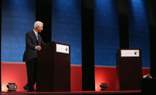Former Florida Gov.  Charlie Crist waits next to an empty podium for Gov. Rick Scott who delayed his entry onto stage for a televised debate due to a dispute over an electric fan. Scott and Crist face off in the governors race. Photo by Joe Raedle/Getty Images