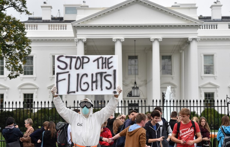 Jeff Hulbert from Annapolis, Maryland, dressed in a protective suit and mask holds a poster demanding for a halt of all flights from West Africa,as he protests outside the White House in Washington, DC on October 16, 2014. Photo by Mladen Antonio/AFP/Getty Images