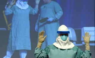Barbara Smith, RN, Mount Sinai Health Sysytems and Bryan Christiansen MD,(monitor-R) CDC Infection Control Team for the Ebola Response demonstrate the proper technique for donning protective gear during an ebola educational session for healthcare workers at the Jacob Javits Center in New York on October 21, 2014.  AFP PHOTO / Timothy A. Clary        Photo by Timothy A. Clary/AFP/Getty Images
