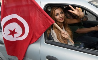 A Tunisian woman waves her national flag as she shows her ink-stained finger after voting in the country's first post-revolution parliamentary election in Tunis on Sunday. Tunisians voted in an election seen as pivotal to establishing democracy in the cradle of the Arab Spring uprisings. Photo by Fadel Senna/AFP/Getty Images