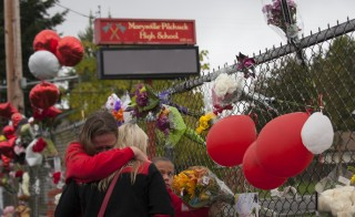 Members of the community and students grieve beside a makeshift memorial at Marysville-Pilchuck High School on Oct. 26, 2014 in Marysville, Washington. High school freshman Jaylen Fryberg shot five students at the high school's cafeteria, killing one and then killing himself on Oct. 24. Of those injured in the shooting, 14-year-old Gia Soriano died Sunday night. Photo by David Ryder/Getty Images
