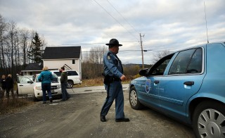 A Maine State Police officer walks in front of the home where Kaci Hickox is staying with her boyfriend Theodore Michael Wilbur on Oct. 30, 2014 in Fort Kent, Maine. After returning from Sierra Leone where she worked with Doctors Without Borders treating Ebola patients, nurse Hickox publicly challenged a quarantine order by the state of Maine. She has twice tested negative for Ebola and says she will lead a normal life unless she feels ill. Photo by Spencer Platt/Getty Images