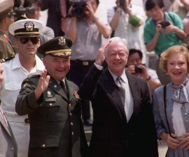 Former President Jimmy Carter (center) waves to the press after he crosses the border into North Korea through the border truce village of Panmunjom for a four-day visit aimed at easing the peninsula's nuclear crisis on June, 15 1994. Photo by Choo Youn-Kong/AFP/Getty Images
