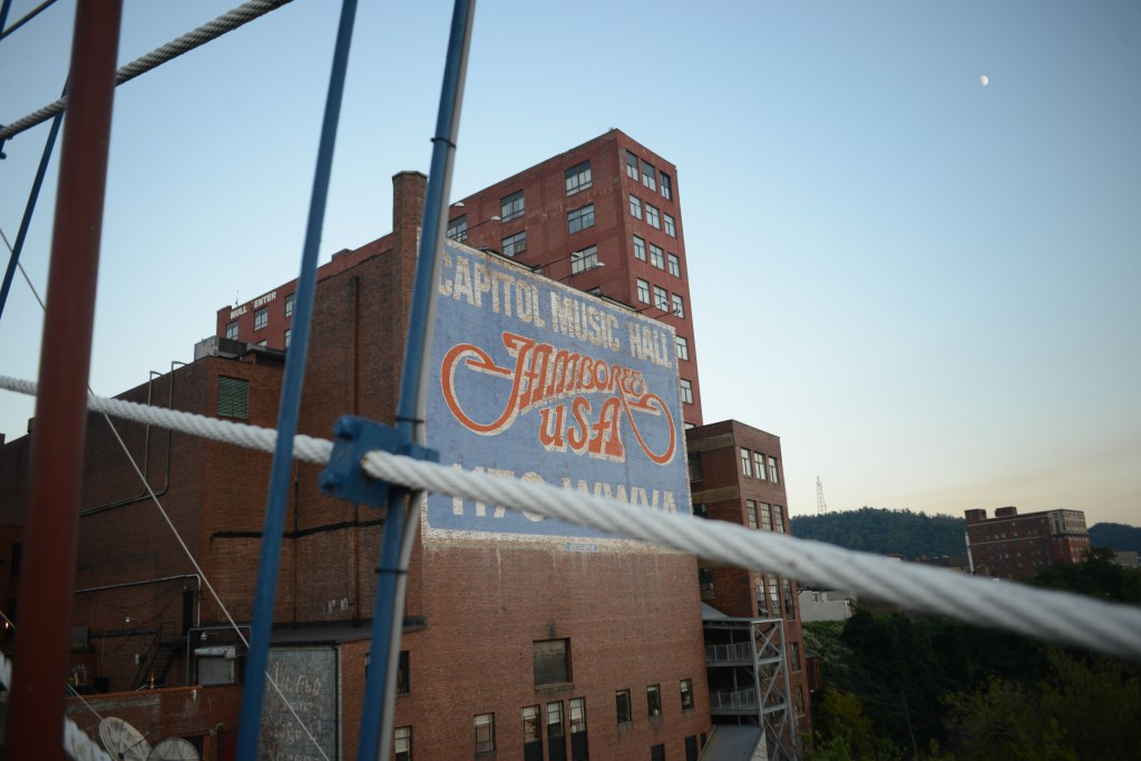 "An advertisement for country music radio show, ""Jamboree USA,"" rises from downtown Wheeling, as seen from the city's famous Suspension Bridge over the Ohio River. Photo by Ariel Min/PBS NewsHour"
