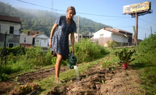 Farm manager Jocelyn Carlson waters the freshly planted vegetables at Farm 18. Photo by Ariel Min/PBS NewsHour