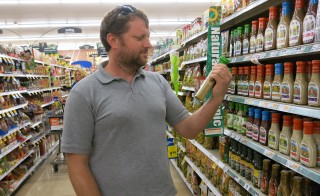 Denver resident Ben Hamilton looks for food labels at a grocery store. Photo courtesy of Luke Runyon, KUNC and Harvest Public Media