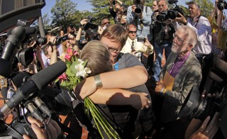Nicole Pries, foreground, and Lindsey Oliver embrace after becoming the first same-sex couple to be married in a ceremony performed by Robin Gorsline in a ceremony outside the John Marshall Court's Building in Richmond, Virginia Oct. 6, 2014. Photo by Jay Paul/Reuters