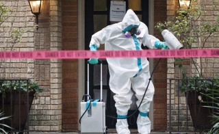 A member of the CG Environmental HazMat team disinfects the entrance to the residence of a health worker at the Texas Health Presbyterian Hospital who has contracted Ebola. Photo by Jaime R. Carrero/Reuters