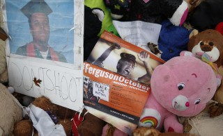"A pamphlet for the "" Ferguson October"" demonstrations is seen on the a makeshift memorial for Michael Brown in Ferguson, Missouri"