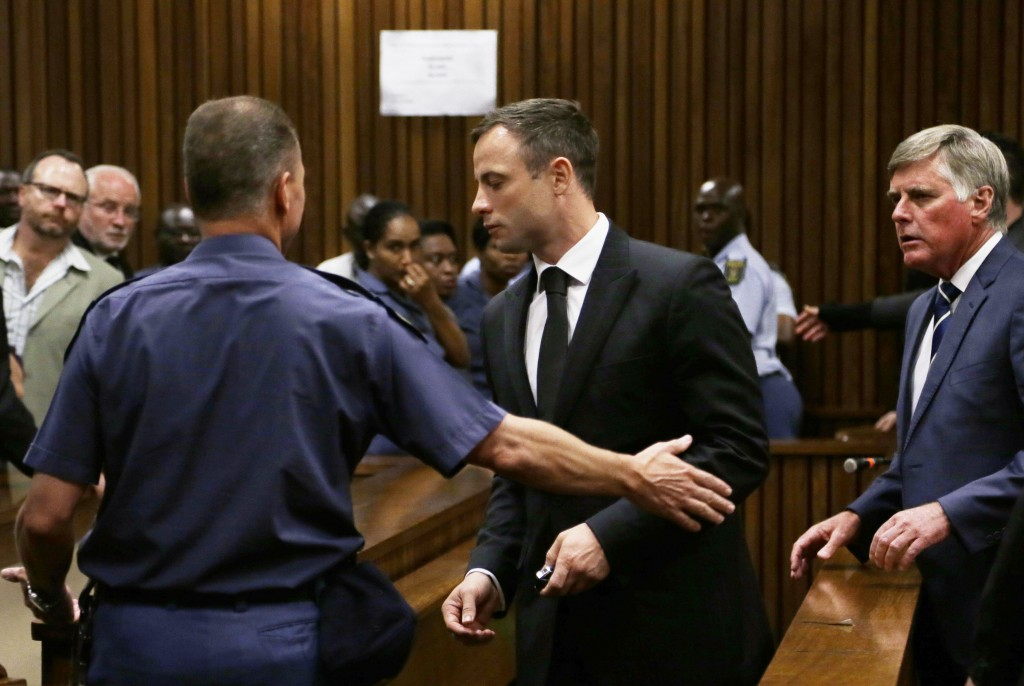 South African Olympic and Paralympic track star Oscar Pistorius is led to holding cells after he was sentenced at the North Gauteng High Court in Pretoria October 21, 2014. A South African judge on Tuesday sentenced Pistorius to five years in prison for the negligent killing of his girlfriend Reeva Steenkamp on Valentine's Day 2013. Photo by REUTERS/Themba Hadebe/Pool
