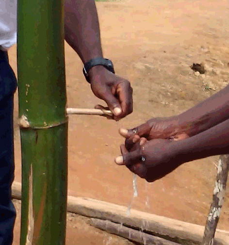 Residents use one of the bamboo hand-washing stations that were set up at entrances to hospitals, county checkpoints and in towns in Liberia. Photo courtesy of the Centers for Disease Control and Prevention