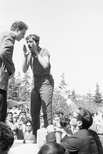 Student activists Jack Weinberg and Mario Savio speaking to each other on top of the police car. Photo by U.C. Berkeley, Bancroft Library