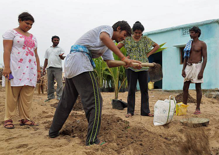 Students from the University of Texas at Austin help plant coconut trees in Markandi, India. Photo courtesy of Nourish International