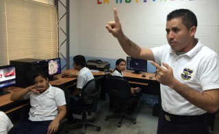 A police officer in Santa Ana, El Salvador teaches a group of sixth graders how to use computers as part of the Gang Resistance Education and Training, or GREAT, program. Photo by Jude Joffe-Block/Fronteras Desk