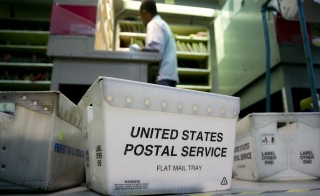 U.S. Postal Service (USPS) crates sit on the floor at the Brookland Post Office in Washington, D.C., U.S.  No customer data was stolen in a recent data breach, USPS officials say. Photo by Andrew Harrer/Bloomberg via Getty Images