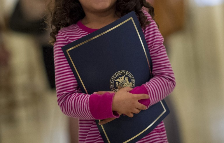 Axa Gutierrez Ramos, 5, holds her Certificate of Honor she received from the Board of Supervisors as she stands for a photograph after attending a San Francisco Board of Supervisors meeting in San Francisco, California, U.S., on Tuesday, Sept. 16, 2014. The San Francisco Board of Supervisors voted unanimously to to draw $2.1 million from a city reserve over the next two years to provide lawyers for undocumented youth and parents with children who are now residing in San Francisco as they await expedited immigration proceedings. Photographer: David Paul Morris/Bloomberg
