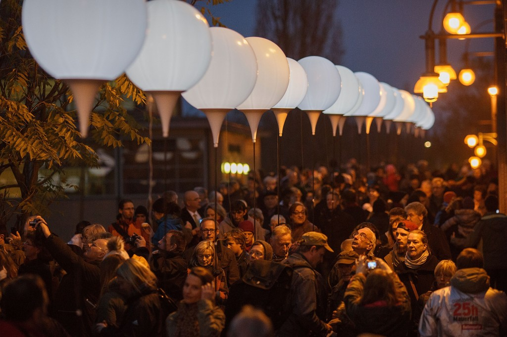 People gather to look the illumination on Boesebruecke bridge in Bornholmer Strasse, where 25 years before thousands of East Germans first crossed unimpeded though a gate of the Berlin Wall into West Berlin, on the 25th anniversary of the fall of the Wall on November 9, 2014 in Berlin, Germany.  Credit: Getty Images