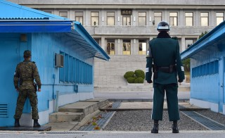 South Korean soldiers stand guard as a North Korean soldier is seen at the truce village of Panmunjom in the Demilitarized Zone dividing the two Koreas on November 12, 2014. Photo by Jung Yeon-Je/Getty Images.