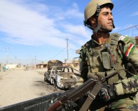 DIYALA, IRAQ - NOVEMBER 24:  A member of a Peshmerga forces stands guard after Iraq army forces and Peshmerga launch an operation against the Islamic State of Iraq and the Levant (ISIL) in Celavle town of Diyala, Iraq on November 24, 2014. Iraqi army forces and Peshmerga regained control of Diyala's Celavle town.  (Photo by Feriq Ferec/Anadolu Agency/Getty Images)