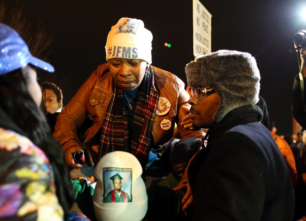 Lesley McSpadden, mother of Michael Brown, is escorted away from in front of the Ferguson police department after a grand jury's decision was delivered in Ferguson, Missouri. Photo by Justin Sullivan/Getty Images