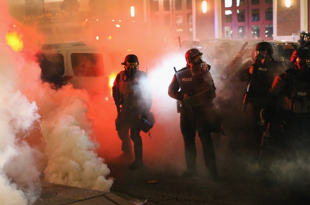 Police guard the Ferguson police department as rioting erupts following the grand jury announcement in the Michael Brown case on November 24.  Photo by Scott Olson/Getty Images
