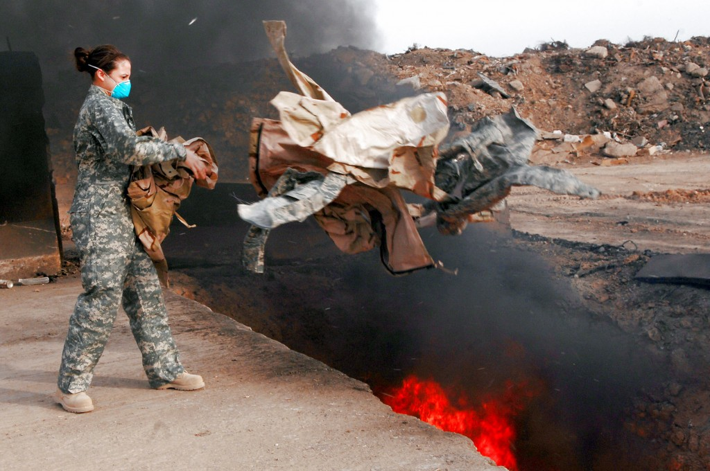 Senior Airman Frances Gavalis tosses unserviceable uniform items into a burn pit March 10 at Balad Air Base, Iraq. Military uniform items must be burned to ensure they cannot be used by opposing forces, according to the U.S. military. Photo by U.S. Air Force/Senior Airman Julianne Showalter