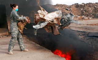 Senior Airman Frances Gavalis tosses unserviceable uniform items into a burn pit March 10 at Balad Air Base, Iraq. Military uniform items turned in must be burned to ensure they cannot be used by opposing forces. Photo by (U.S. Air Force photo/Senior Airman Julianne Showalter