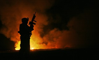 Sgt. Robert B. Brown watches over the civilian Fire Fighters at the burn pit at camp Fallujah, Iraq as smoke and flames rise into the night sky behind him on May 25th, 2007. Official USMC photograph by Cpl. Samuel D. Corum