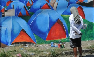 A man looks at a mural of painted tents on a wall of a cemetery in Tacloban in central Philippines on Friday. Today marks the year anniversary of Typhoon Haiyan, which left 4.1 people displaced in the Philippines. Photo by TED ALJIBE/AFP/Getty Images