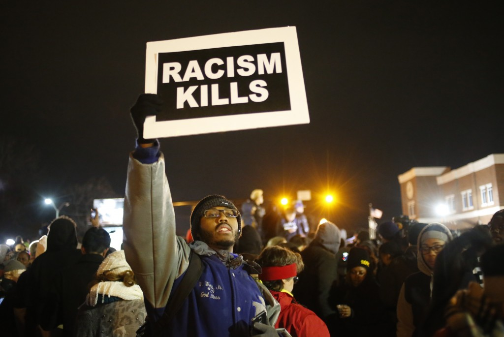 A protester holds a sign outside the Ferguson Police Department in Ferguson, Missouri. REUTERS/Adrees Latif