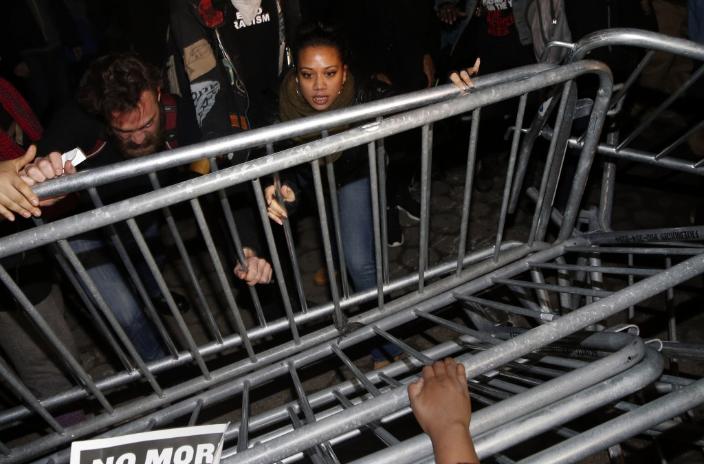 Demonstrators push down New York Police Department (NYPD) barricades during a protest against the verdict announced in the shooting death of unarmed black teenager Michael Brown, at Union Square in New York. Photo by REUTERS/Shannon Stapleton