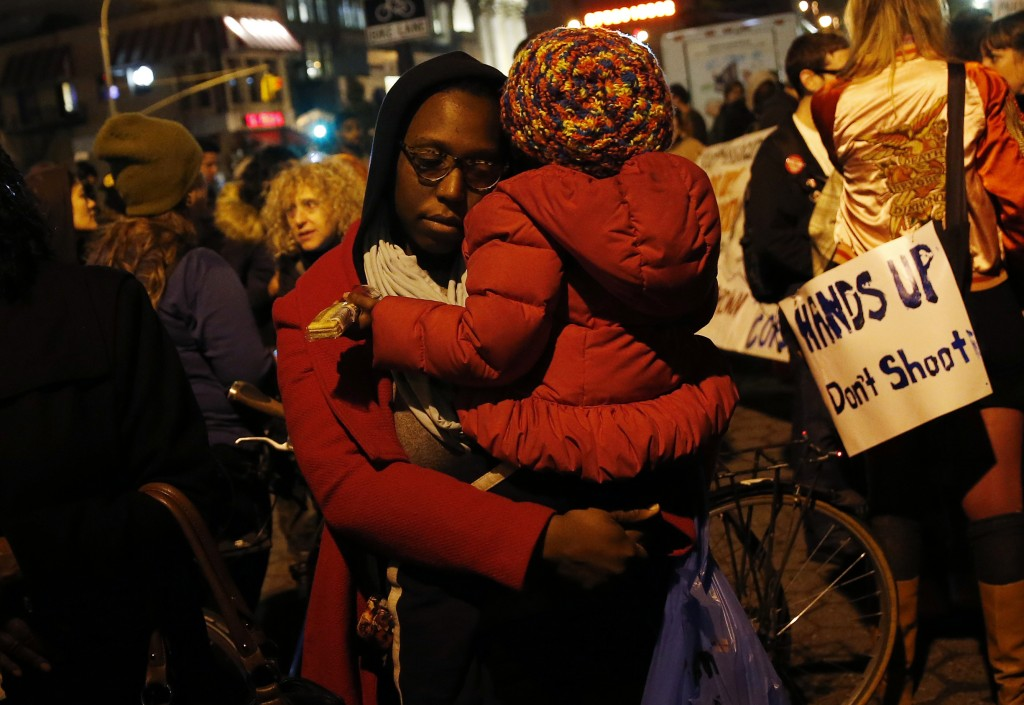 A woman at Union Square in New York holds a child before the verdict was announced in the shooting death of unarmed black teenager Michael Brown.  Photo by Shannon Stapleton/Reuters