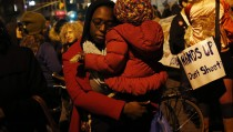 A woman holds a child before the verdict was announced in the shooting death of unarmed black teenager Michael Brown, at Union Square in New York November 24, 2014.  Photo by Shannon Stapleton/Reuters