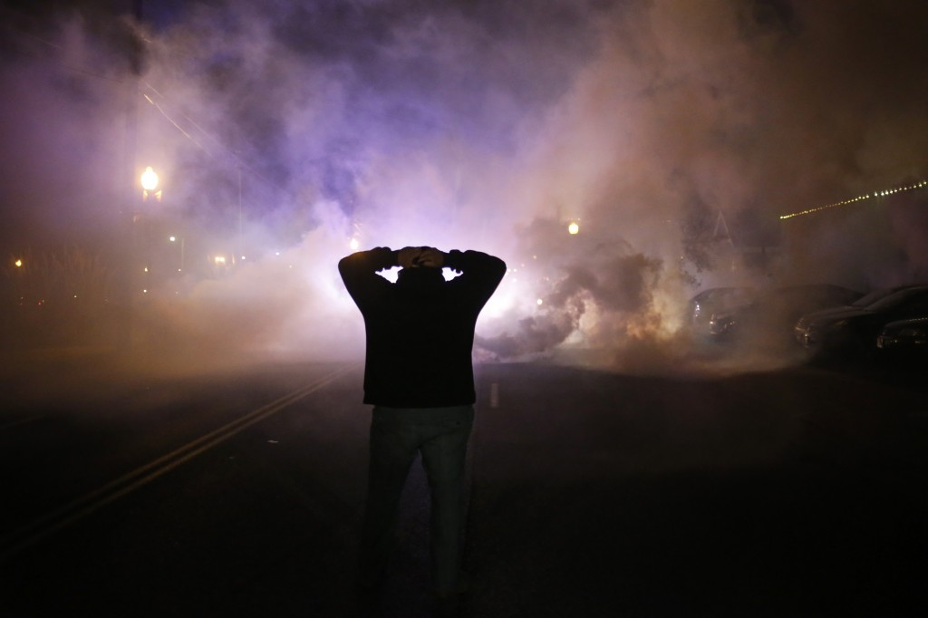 A protester stands with his hands on his head as a cloud of tear gas approaches after a grand jury returned no indictment in the shooting of Michael Brown in Ferguson, Missouri, November 24, 2014.  Photo by Adrees Latif  / Reuters