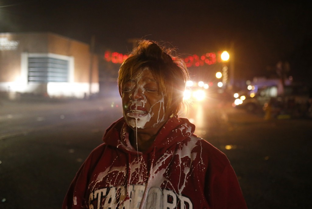 A protester stands in the street after being treated for tear gas exposure after a grand jury returned no indictment. Photo by Adrees Latif / Reuters