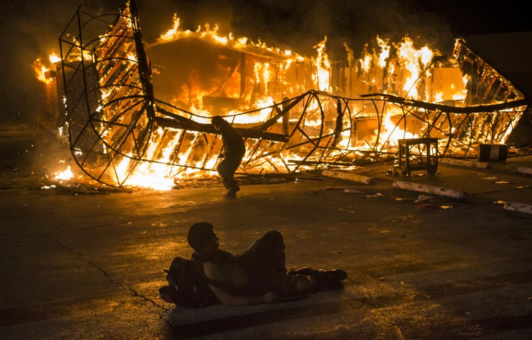 A resident, lying shirtless, keeps warm as another approaches the blazing skeleton of Juanita's Fashions R Boutique after it was burned to the ground in Ferguson, Missouri early morning November 25, 2014. REUTERS/Adrees Latif