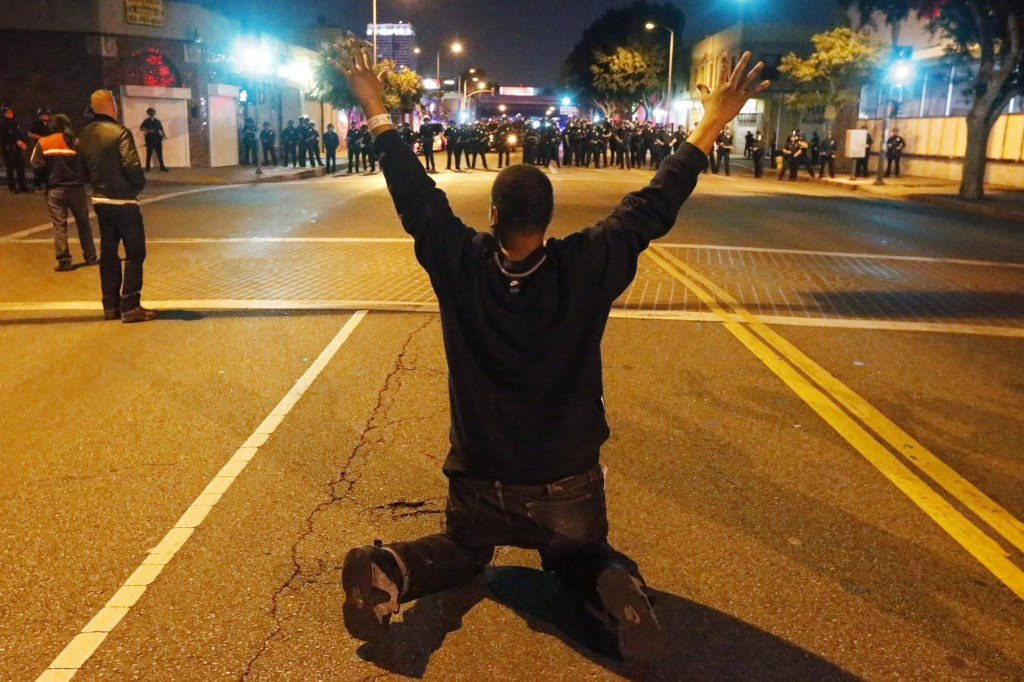 A man kneels in the road in front of a line of police during a demonstration in Los Angeles, California November 24, 2014, following the grand jury decision in the shooting of Michael Brown. REUTERS/Lucy Nicholson