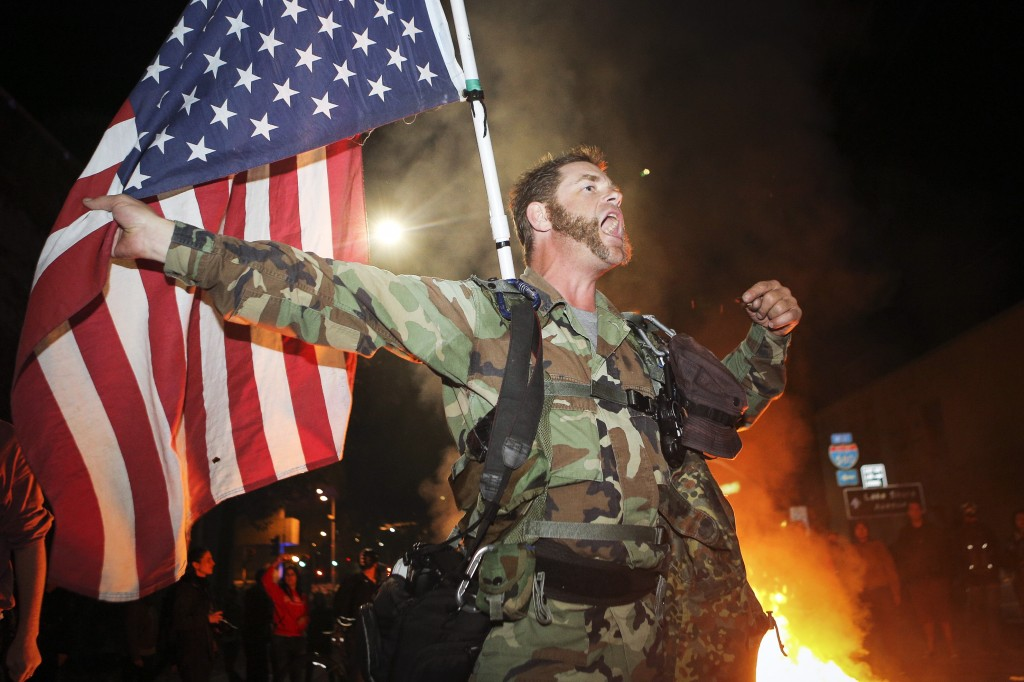 James Cartmill of Veterans for Peace holds an American flag upside down to indicate distress during a demonstration in Oakland, California November 24. Photo by Elijah Nouvelage / REUTERS